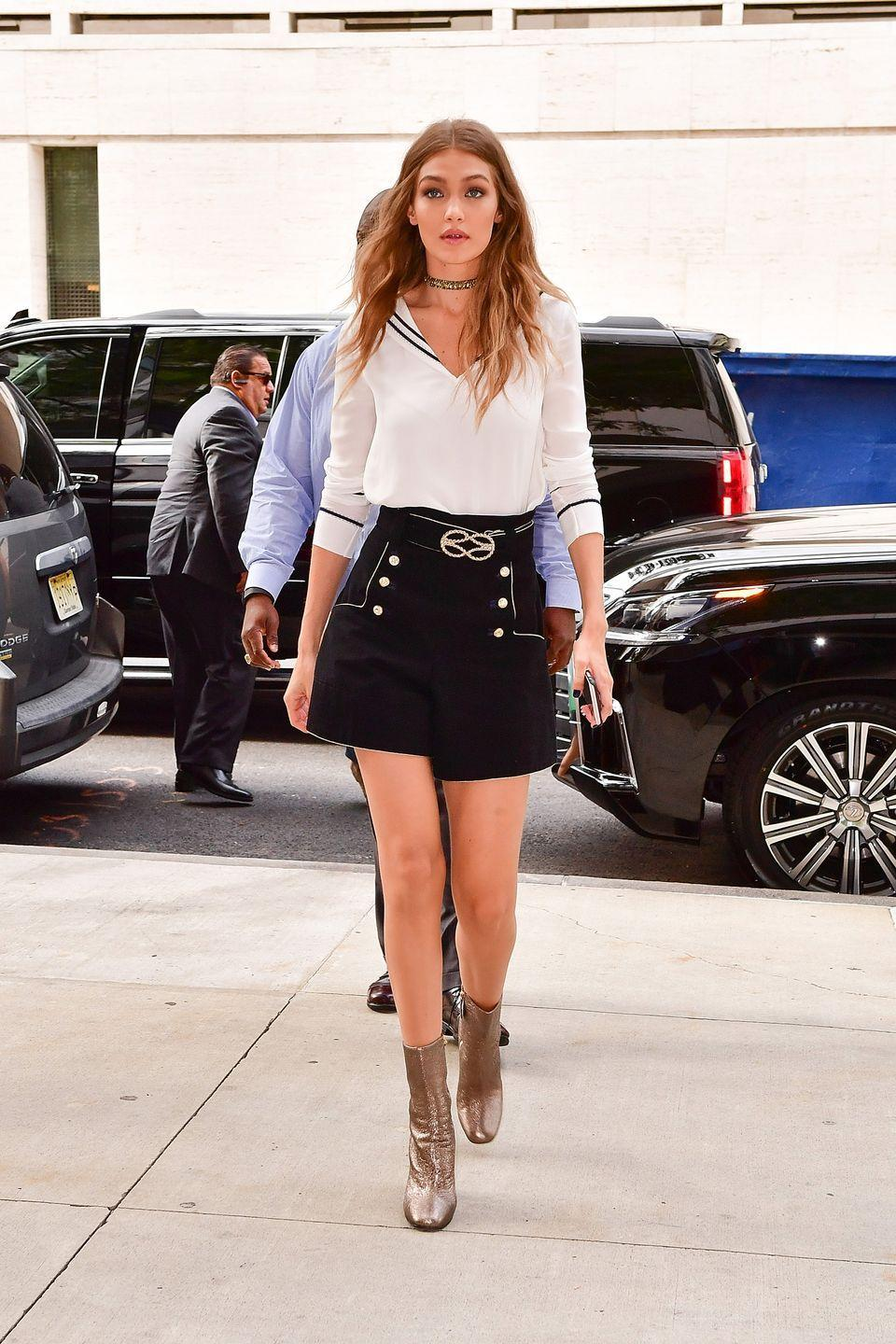 <p>Keeping up with the nautical theme of her Tommy Hilfiger collab, Hadid wears a sailor-esque blouse, belted high-waisted shorts with button details, metallic boots and a choker to her Tommy x Gigi press conference in NYC.</p>