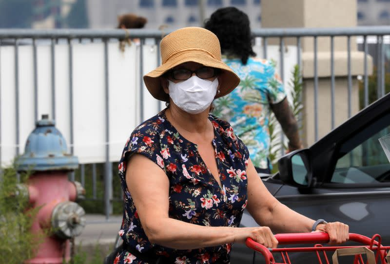 People wear protective face masks outside at a shopping plaza in Edgewater New Jersey