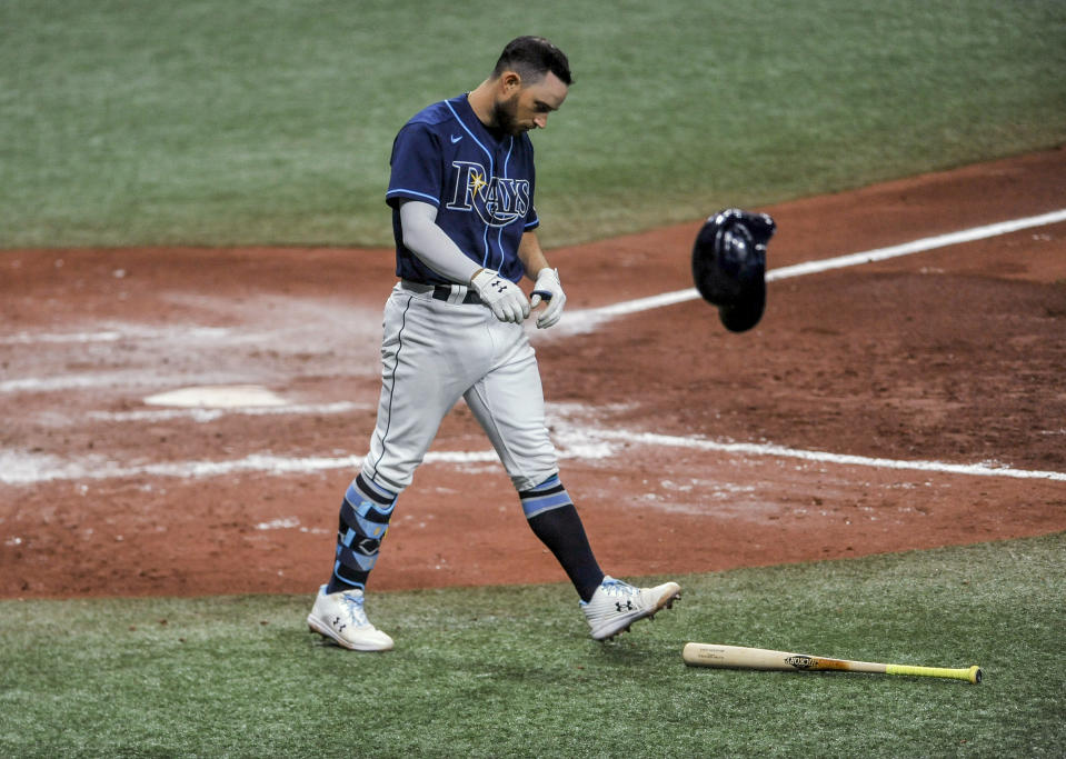 Tampa Bay Rays' Brandon Lowe tosses his helmet after striking out during the sixth inning of the team's baseball game against the Texas Rangers on Wednesday, April 14, 2021, in St. Petersburg, Fla. (AP Photo/Steve Nesius)