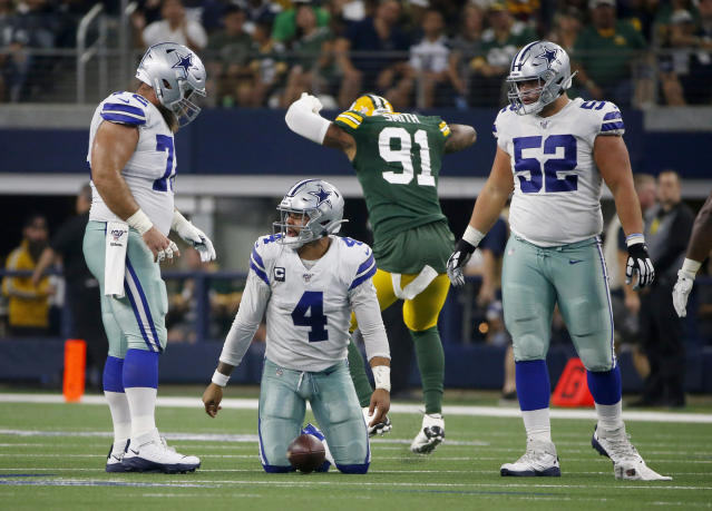 Cowboys linemen Travis Frederick (L) and Connor Williams (R) watch Dak Prescott get up after getting sacked by the Packers' Preston Smith. Prescott was sacked a total of three times in Sunday's loss. (AP)