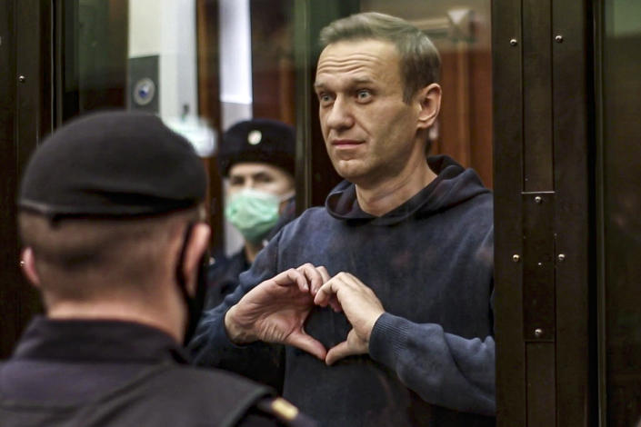 In this handout photo taken from a footage provided by Moscow City Court, Russian opposition leader Alexei Navalny shows a heard symbol standing in the cage during a hearing to a motion from the Russian prison service to convert the suspended sentence of Navalny from the 2014 criminal conviction into a real prison term in the Moscow City Court in Moscow, Russia, Tuesday, Feb. 2, 2021. A Moscow court has ordered Russian opposition leader Alexei Navalny to prison for more than 2 1/2 years for violating the terms of his probation while he was recuperating in Germany from nerve-agent poisoning. Navalny, who is the most prominent critic of President Vladimir Putin, had earlier denounced the proceedings as a vain attempt by the Kremlin to scare millions of Russians into submission. (Moscow City Court via AP)