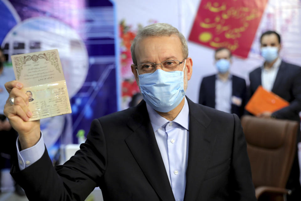 Former Iranian parliament speaker Ali Larijani shows his identification document while registering his name as a candidate for the June 18 presidential elections at elections headquarters of the Interior Ministry in Tehran, Iran, Saturday, May 15, 2021. (AP Photo/Ebrahim Noroozi)