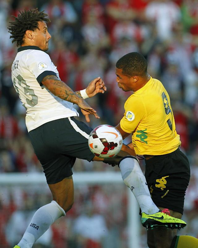 U.S. midfielder Jermaine Jones (13) and Jamaica forward Ryan Johnson (9) go up for the ball in the first half of a World Cup qualifier soccer match at Sporting Park in Kansas City, Kan., Friday, Oct. 11, 2013. (AP Photo/Colin E. Braley)