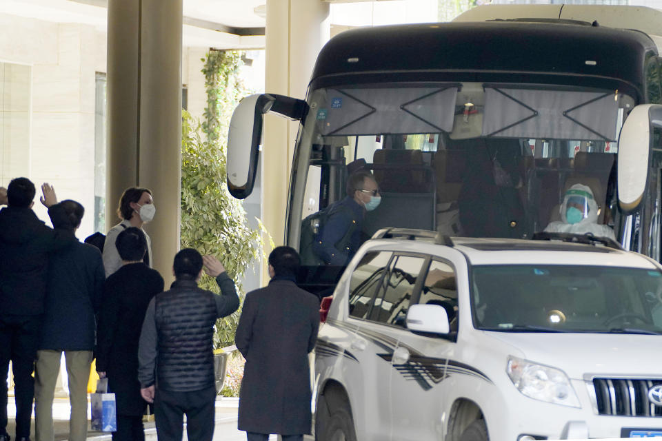 Workers wave to the team of experts from the World Health Organization who ended their quarantine and prepare to leave the quarantine hotel by bus in Wuhan in central China's Hubei province on Thursday, Jan. 28, 2021. (AP Photo/Ng Han Guan)