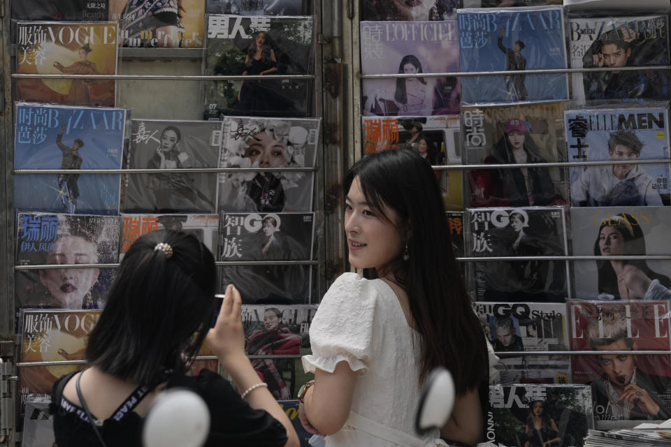 A woman poses for a photo near magazines showing celebrities at a newsstand in Beijing on Aug. 1, 2021. Hugely popular online games and celebrity culture are the latest targets in the ruling Communist Party's campaign to encourage China's public to align their lives with its political and economic goals. (AP Photo/Ng Han Guan)
