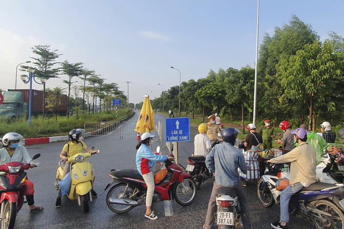 People are turned away at a checkpoint at an entrance to Hanoi, Vietnam, Saturday, July 24, 2021. Vietnam announced a 15-day lockdown in the capital Hanoi starting Saturday as a coronavirus surge spread from the southern Mekong Delta region. (AP Photo/Hieu Dinh)