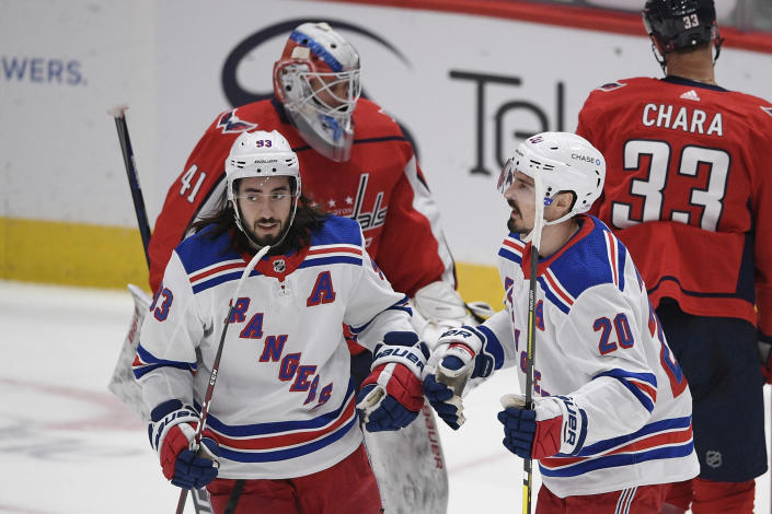 New York Rangers left wing Chris Kreider (20) celebrates his goal with center Mika Zibanejad (93) during the first period of an NHL hockey game against Washington Capitals goaltender Vitek Vanecek (41), Saturday, Feb. 20, 2021, in Washington. (AP Photo/Nick Wass)