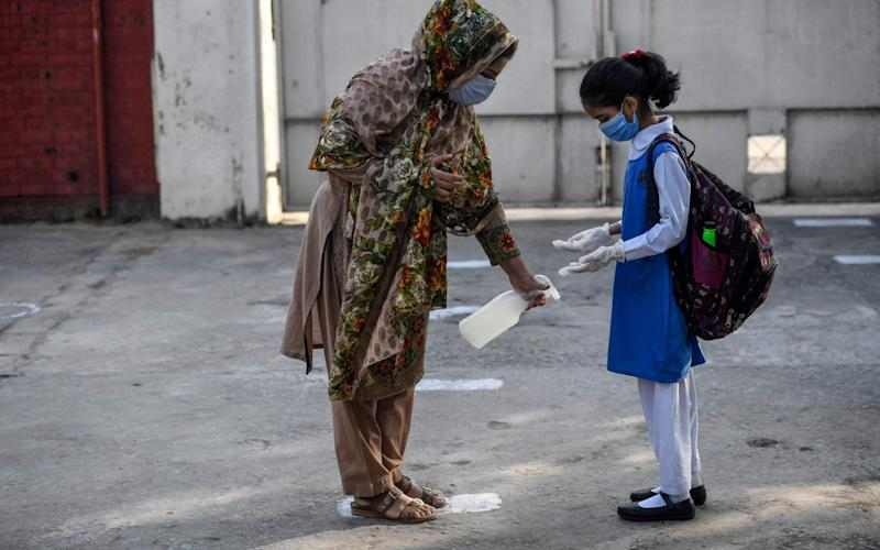 A teacher sprays disinfectant on the shoes of a child wearing a facemask and gloves at the entrance of a junior campus school upon arrival in Islamabad - AFP