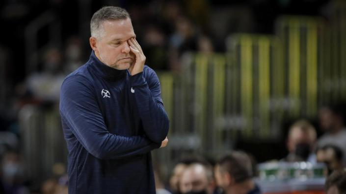 Denver Nuggets coach Michael Malone rubs his eye in the first quarter of a preseason NBA basketball game against the Minnesota Timberwolves in Denver, Friday, Oct. 8, 2021. (AP Photo/Joe Mahoney)