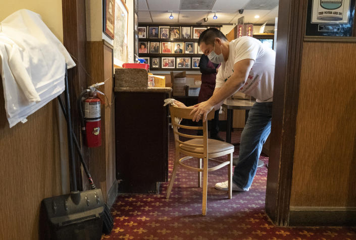 Benny Yun, owner of Yang Chow restaurant sanitizes a chair in Los Angeles, Thursday, Dec. 17, 2020. Bigotry toward Asian Americans and Asian food has spread steadily alongside the coronavirus in the United States. Yun said even though his businesses have survived the pandemic, they get prank calls almost daily asking if they have dog or cat on the menu or impersonating a thick Asian accent. (AP Photo/Damian Dovarganes)