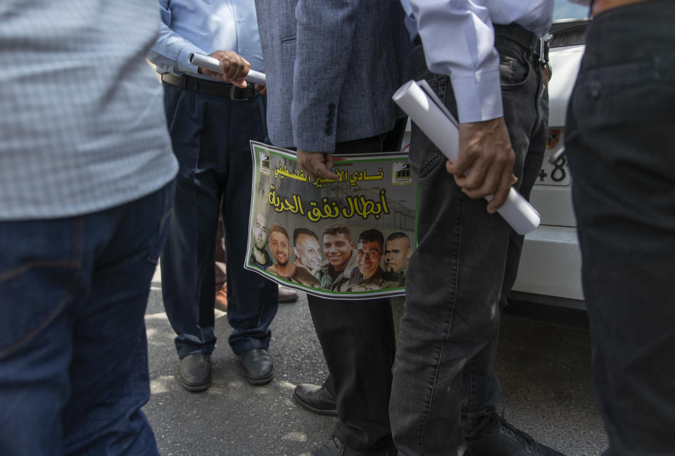 """A Palestinian man carries a poster with pictures of the six Palestinian prisoners who escaped from an Israeli jail that says """"heroes of the freedom tunnel,"""" during a protest supporting prisoners, in the West Bank city of Ramallah, Tuesday, Sept. 14, 2021. The cinematic escape of six prisoners who tunneled out of an Israeli penitentiary shone a light on Israel's mass incarceration of Palestinians, one of the many bitter fruits of the conflict. (AP Photo/Nasser Nasser)"""