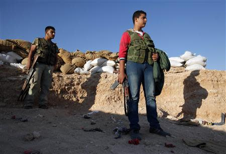Free Syrian Army fighters stand with their weapons in a trench where sandbags are piled near the Kwers military airport, where forces loyal to Syria's President Bashar al-Assad are based, in Aleppo September 9, 2013. REUTERS/Loubna Mrie