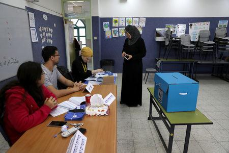 An Israeli-Arab woman prepares to casts her ballot as Israelis vote in a parliamentary election, at a polling station in Umm al-Fahm, Israel April 9, 2019. REUTERS/Ammar Awad