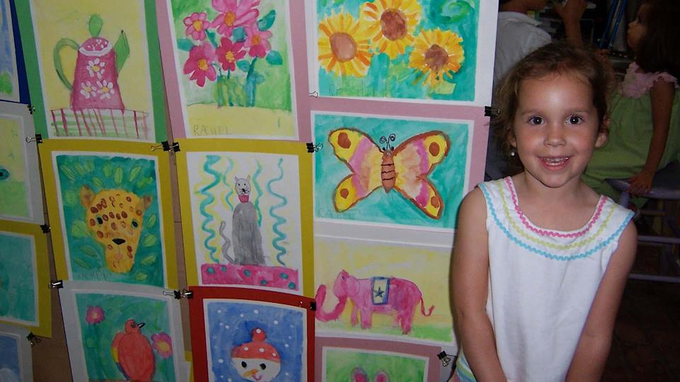 Heck as a child smiling in front of her artwork.