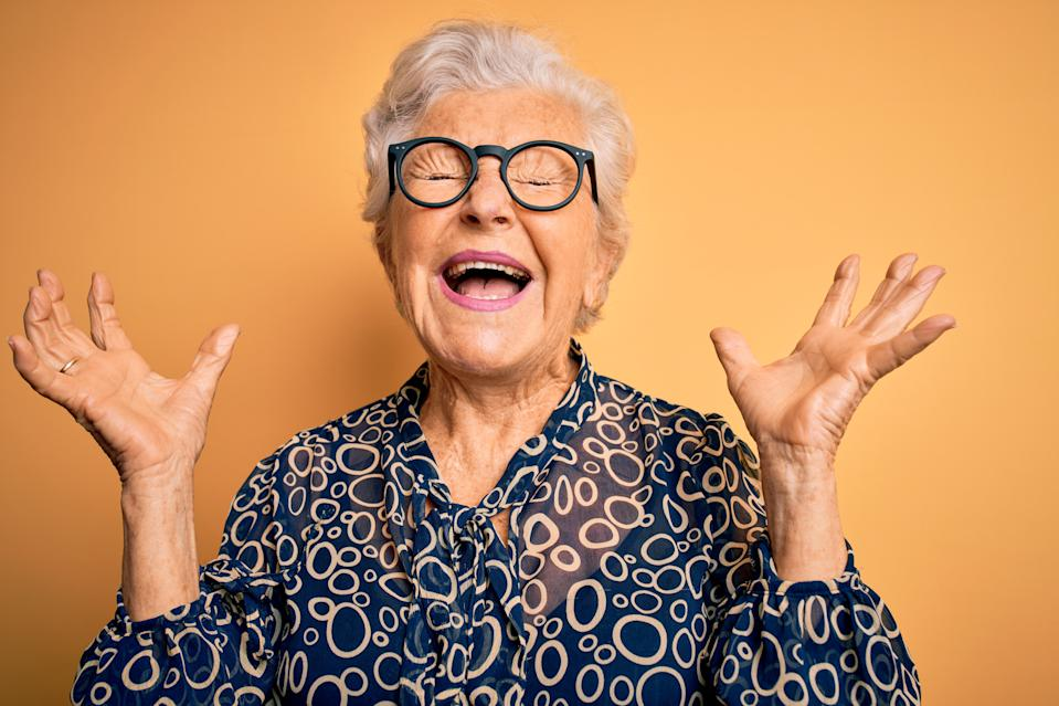 Senior beautiful grey-haired woman wearing casual shirt and glasses over yellow background celebrating mad and crazy for success with arms raised and closed eyes screaming excited. Winner concept