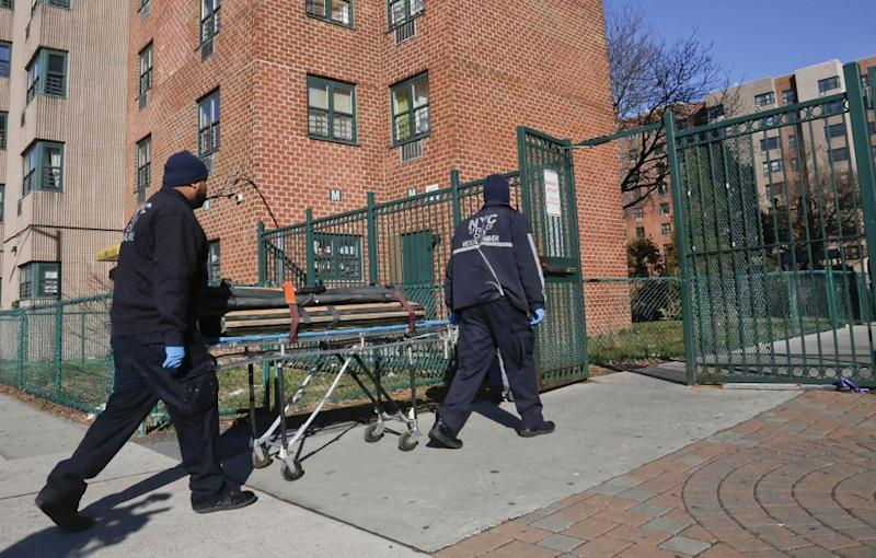 Officials from the medical examiner's office head to the Brooklyn apartment where four people were found shot to death