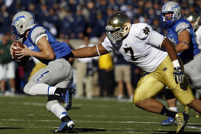 Air Force quarterback Nate Romine, left, eludes the rush of Notre Dame defensive lineman Stephon Tuitt in the first quarter of an NCAA college football game in Air Force Academy, Colo., Saturday, Oct. 26, 2013. (AP Photo/David Zalubowski)