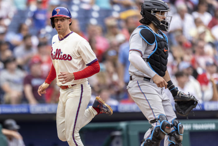 Philadelphia Phillies' Brad Miller runs by Miami Marlins catcher Jorge Alfaro to score during the sixth inning of a baseball game Sunday, July 18, 2021, in Philadelphia. (AP Photo/Laurence Kesterson)