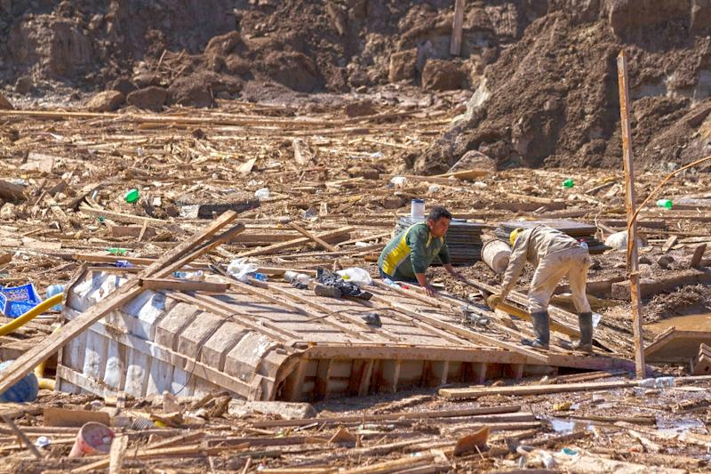People search among the rubble in an area which was flooded in Chanaral, northern Chile, on April 1, 2015