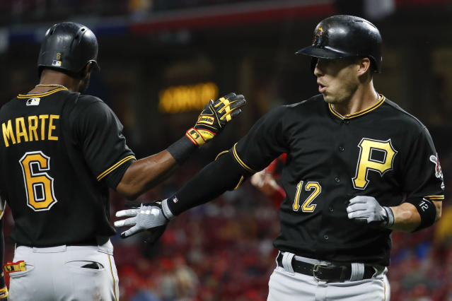 Pittsburgh Pirates' Corey Dickerson (12) celebrates with Starling Marte (6) after hitting a solo home run off Cincinnati Reds starting pitcher Anthony DeSclafani in the fifth inning of a baseball game, Saturday, July 21, 2018, in Cincinnati. (AP Photo/John Minchillo)