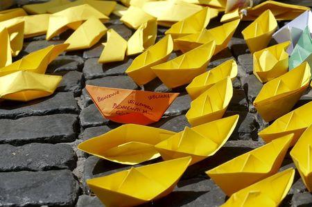"""Paper boats are seen in the pavement during a flash mob organized by Amnesty International Italy to promote the campaign """"SOS Europe, people before borders"""" in downtown Rome"""