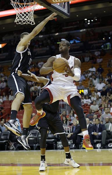 Miami Heat shooting guard Dwyane Wade (3) prepares to pass against Brooklyn Nets center Brook Lopez (11) in the first period of an NBA preseason basketball game, Friday, Oct. 25, 2013, in Miami. (AP Photo/Alan Diaz)