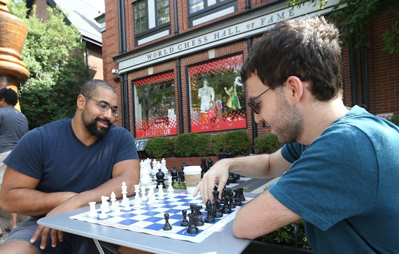 Grandmaster Robert Hess gives former Baltimore Ravens offensive lineman John Urschel a chess lesson outside the Chess Club and Scholastic Center in St. Louis on August 13, 2017. (BILL GREENBLATT via Getty Images)
