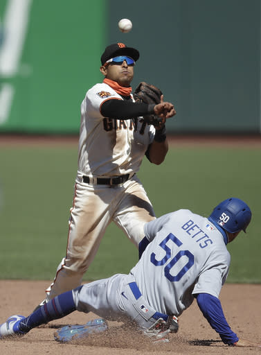 San Francisco Giants' Donovan Solano, top, throws over Los Angeles Dodgers' Mookie Betts to complete a double play in the sixth inning of the first game of a baseball doubleheader Thursday, Aug. 27, 2020, in San Francisco. Dodger's Corey Seager was out at first base. (AP Photo/Ben Margot)