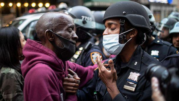 PHOTO: A protester and an officer shake hands in the middle of a standoff during a rally calling for justice over the death of George Floyd Tuesday, June 2, 2020, in New York. Floyd died after being restrained by Minneapolis police officers on May 25. (Wong Maye-e/AP)