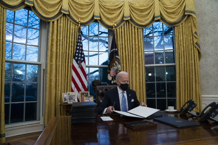 FILE - In this Jan. 20, 2021, file photo President Joe Biden signs a series of executive orders in the Oval Office of the White House in Washington. (AP Photo/Evan Vucci, File)