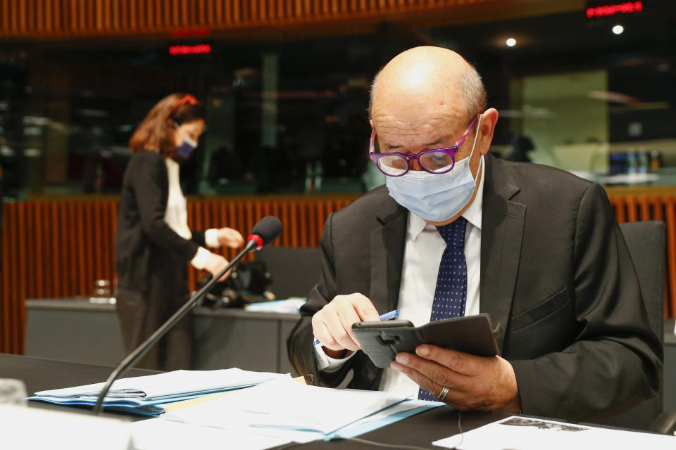 French Foreign Minister Jean-Yves Le Drian looks at his smartphone as he attends a European Foreign Affairs Ministers meeting at the European Council building in Luxembourg, Monday, June 21, 2021. EU foreign ministers were set to approve Monday a new set of sanctions against scores of officials in Belarus and prepare a series of measures aimed at the country's economy. (Johanna Geron/Pool Photo via AP)