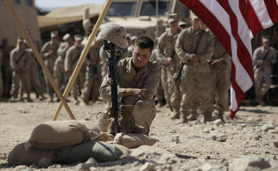 U.S. Marine Cpl. Russell pays his respects to Lance Cpl. Joshua Bernard during a memorial service at a forward operating base with Golf Company, 2nd Battalion, 3rd Regiment, 2nd MEB, 3rd MEF, Thursday, Aug. 27, 2009, in Now Zad in the Helmand Province of Afghanistan. Bernard was killed during a Taliban ambush on Aug. 14. (AP Photo/Julie Jacobson, File)