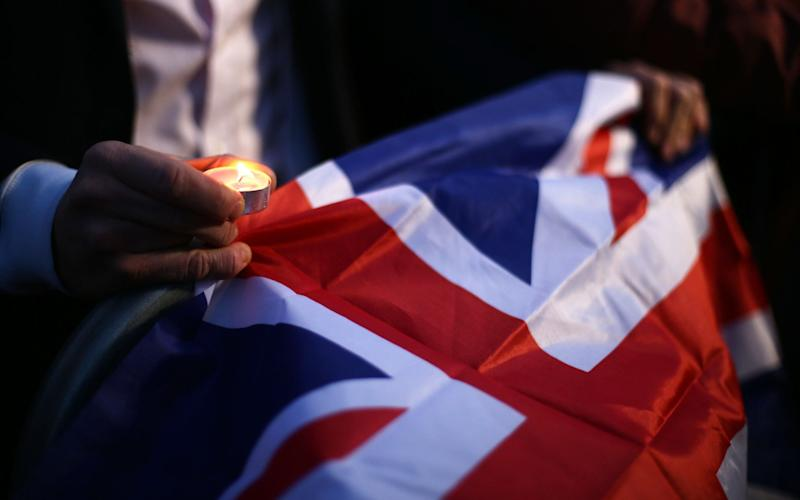 A member of the public holds a candle and Union Jack flag during the candlelight vigil in Trafalgar Square, London to remember those who lost their lives in the Westminster terrorist attack. - Yui Mok/PA Wire
