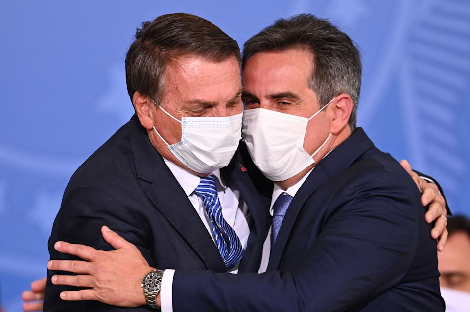 Brazilian President Jair Bolsonaro (L) hugs Brazilian senator Ciro Nogueira during a ceremony where he officially takes office as Chief of Staff, at Planalto Palace in Brasilia, on August 4, 2021. - A Supreme Court justice ruled on Wednesday President Jair Bolsonaro should be investigated for unproven claims Brazil's electronic voting system is riddled with fraud, adding the far-right leader to an ongoing probe on the spread of fake news by his government. (Photo by EVARISTO SA / AFP) (Photo by EVARISTO SA/AFP via Getty Images)