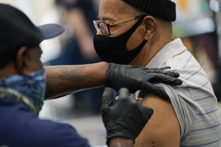 """Wayne Pollard receives a COVID-19 vaccine at the Martin Luther King Senior Center, Wednesday, Feb. 10, 2021, in North Las Vegas. The """"pop-up"""" clinic was held to serve under-vaccinated areas in Las Vegas. (AP Photo/John Locher)"""