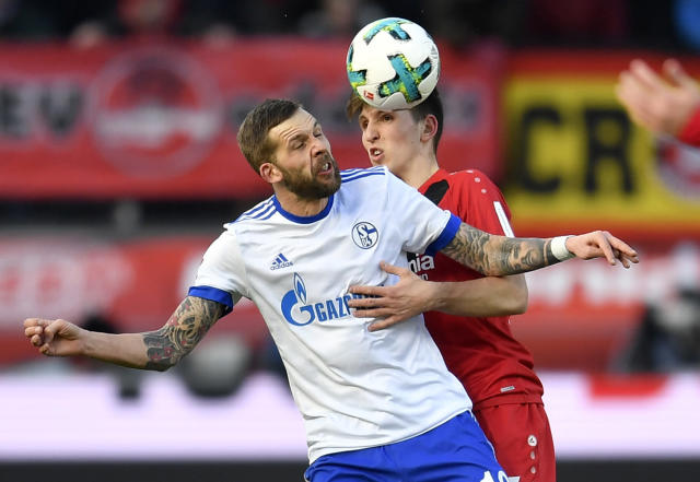 Leverkusen's Panagiotis Retsos, right, and Schalke's Guido Burgstaller challenge for the ball during the German Bundesliga soccer match between Bayer Leverkusen and FC Schalke 04 in Leverkusen, Germany, Sunday, Feb 25, 2018. (AP Photo/Martin Meissner)