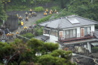 Houses are damaged by a mudslide following heavy rains at the Izusan district in Atami, Shizuoka prefecture, west of Tokyo, Sunday, July 4, 2021. The mudslide carrying a deluge of black water and debris crashed into rows of houses in the town following heavy rains on Saturday, leaving multiple people missing, officials said. (AP Photo/Eugene Hoshiko)