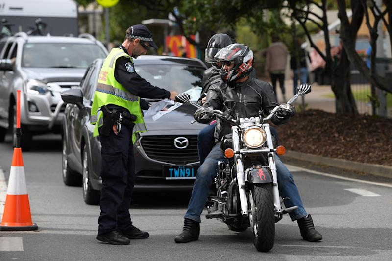 Police talk to a man and passenger on a motorcycle trying to cross the Queensland/NSW border.