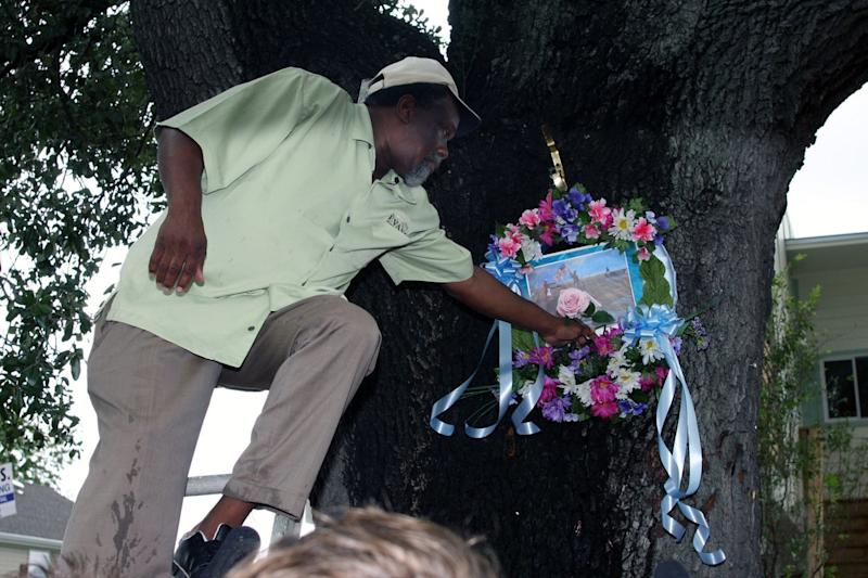 On the fifth anniversary of Hurricane Katrina's landfall, Robert Green Sr. places a flower in a wreath on the tree in the Lower Ninth Ward in New Orleans where his mother and granddaughter sought refuge before ultimately being swept away to their deaths: Getty Images