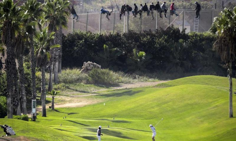 Migrants sit atop a border fence during an attempt to cross from Morocco into the Spanish exclave of Melilla.