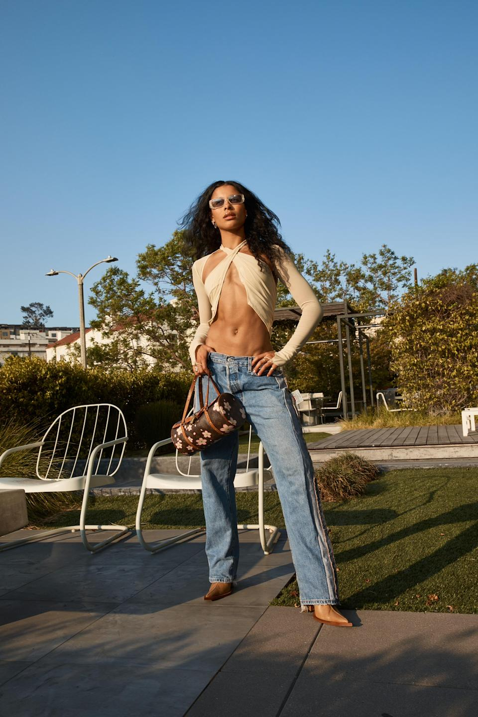 Miro wears a Sami Miro Vintage open seam scarf top in ivory mesh and porterhouse jeans in vintage blue with vintage Louis Vuitton purse and Versace sunglasses.