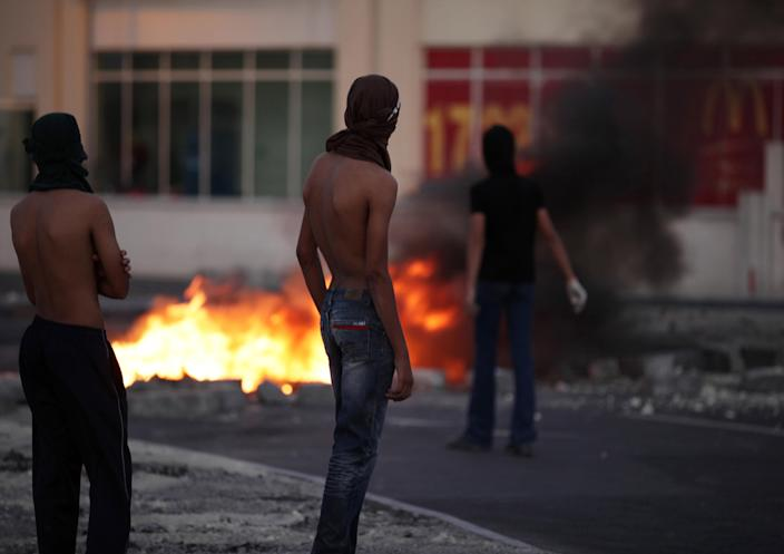 """Masked Bahraini anti-government protesters watch for riot police as tires burn on a street in the western village of Malkiya, Bahrain, Tuesday, Aug. 13, 2013. Inspired by the movement behind Egypt's military coup, pro-democracy activists in Bahrain are hoping to gain new momentum by calling for nationwide protests Wednesday. Authorities warned they will """"forcefully confront"""" any large demonstrations, raising fears of more violence in the strategic Gulf kingdom. (AP Photo/Hasan Jamali)"""