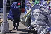 """Sotero Cirilo airs out a sleeping bag at the homeless encampment where he sleeps in the Queens borough of New York, Tuesday, April 13, 2021. The 55-year-old immigrant from Mexico used to make $800 per week at two Manhattan restaurants, which closed when the COVID-19 pandemic started. A few months later, he couldn't afford the rent of his Bronx room, and afterward, of another room in Queens he moved into. """"I never thought I would end up like this, like I am today,"""" he said, his eyes filling up with tears. (AP Photo/Seth Wenig)"""