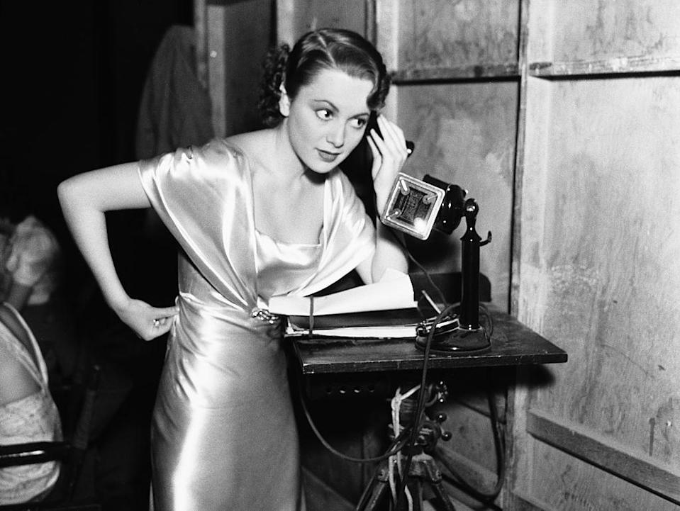 <p>Olivia standing with the telephone up to her ear.</p>