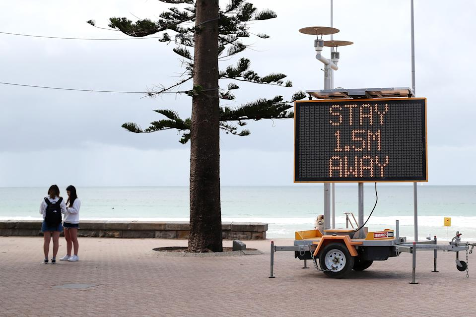 A sign reminding residents and tourists of new social distancing rules is displayed at Manly Beach on March 23, 2020 in Sydney, Australia. From midday Monday, venues such as bars, clubs, nightclubs, cinemas, gyms and restaurants, along with anywhere people remain static would be closed. Schools remain open but parents have the option to keep children at home if they wish while Victoria is bringing forward school holidays from Tuesday. There are now 1353 confirmed cases of COVID-19 In Australia and the death toll now stands at seven.