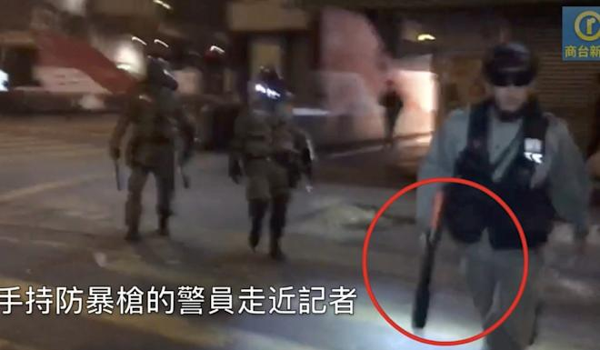 Another screen grab from the video depicting the incident, showing an officer holding what appears to be a gun for crowd control. Photo: Commercial Radio