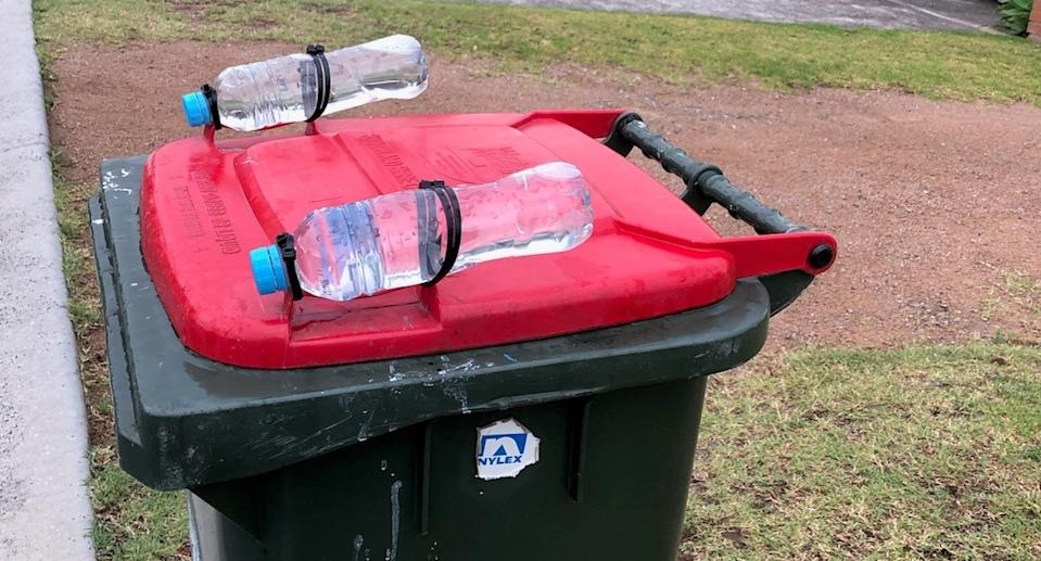 A garbage bin with water bottles tied to it.
