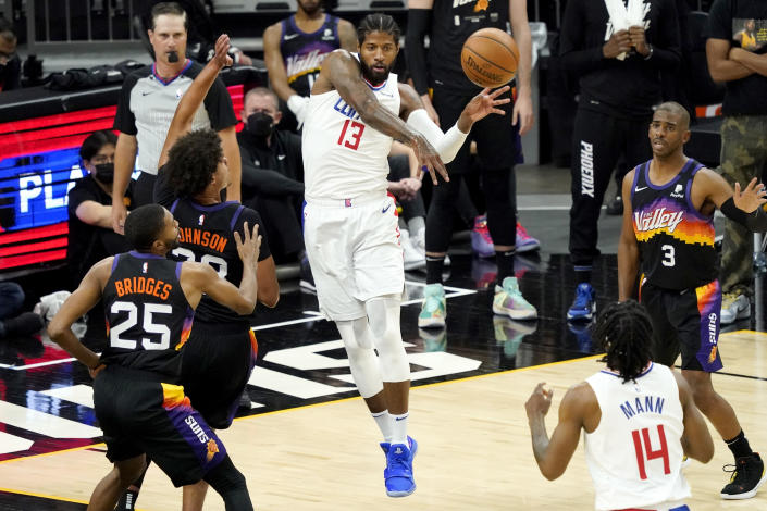 Los Angeles Clippers guard Paul George (13) passes as Phoenix Suns forward Cameron Johnson (23) looks on during the first half of game 5 of the NBA basketball Western Conference Finals, Monday, June 28, 2021, in Phoenix. (AP Photo/Matt York)