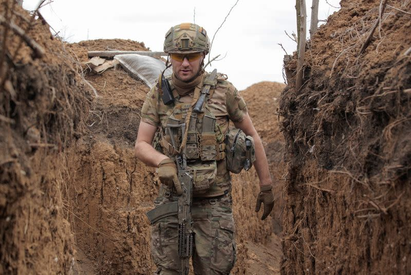 A service member of the Ukrainian armed forces walks with a weapon at fighting positions near the rebel-controlled city of Donetsk
