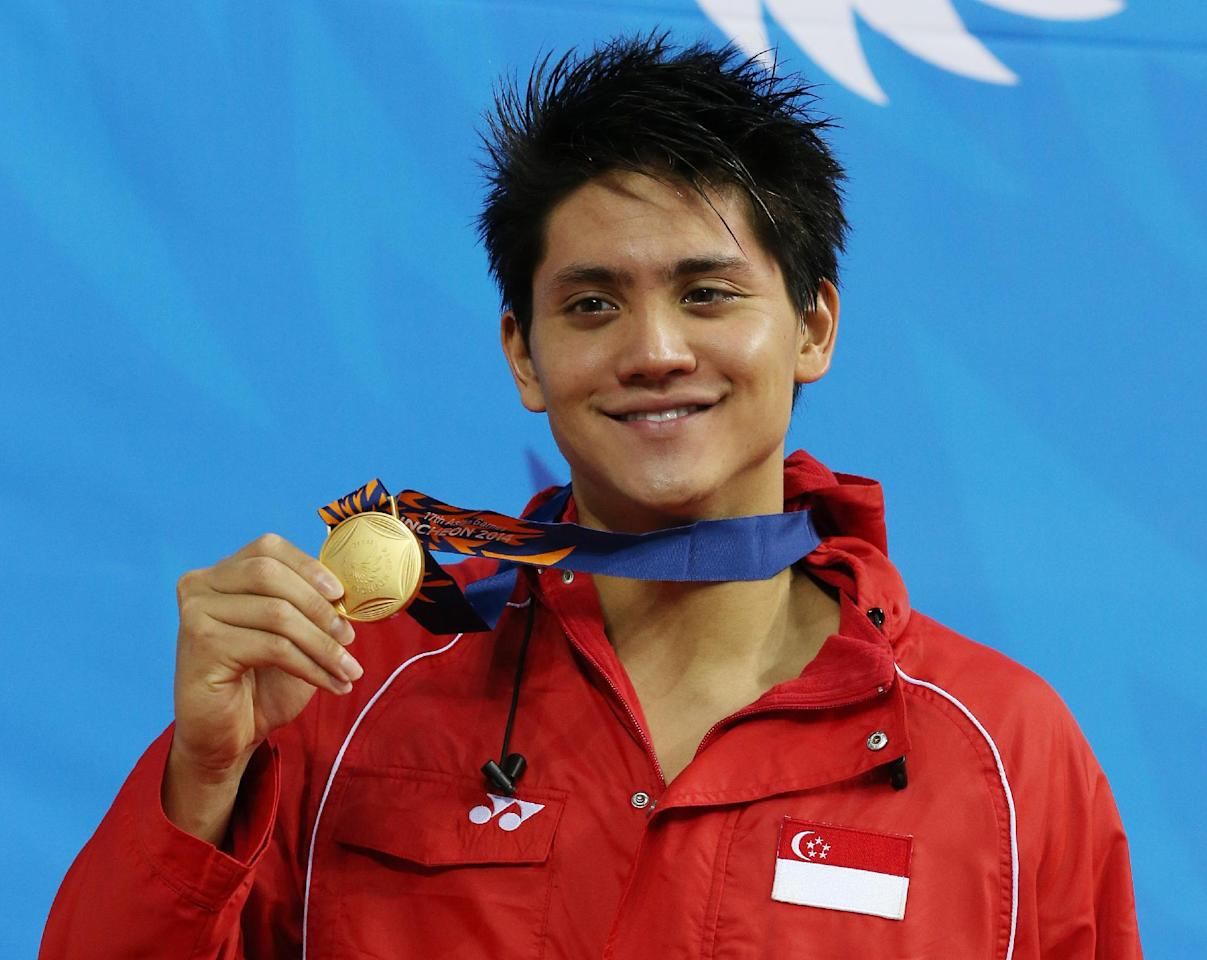 Singapore's Joseph Schooling holds up his gold medal after winning the men's 100-meter butterfly swimming final at the 17th Asian Games in Incheon, South Korea,  Wednesday, Sept. 24, 2014.(AP Photo/Rob Griifith)